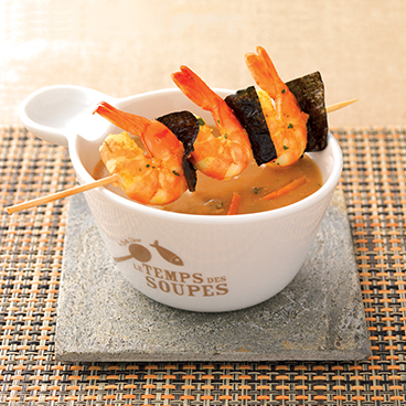 Cream of shellfish soup with prawn skewers